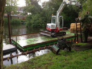 Met trilblok worden de palen geplaatst en later de gehele constructie naar beneden gedrukt tot 20 cm onder water.